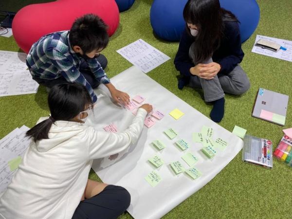 ドルトン東京学園での中学生向け読書会の様子。ピンクの付せんには「良くなっていると思うこと」、緑の付せんには「悪くなっていると思うこと」をそれぞれ書き込んだ